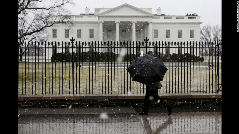 A man walks in front of the White House as snow and rain hit the Washington area on March 6.