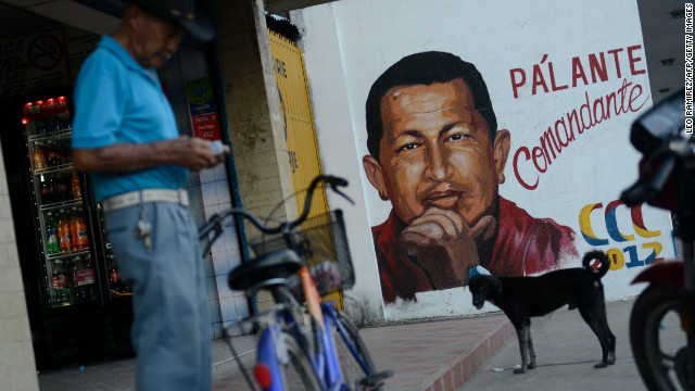 A man stands next to a campaign poster of Venezuelan President Hugo Chavez on September 26, 2012 in Sabaneta, Barinas, the birthplace of Chavez, ahead of the upcoming October 7th election. Chavez, in power since 1999, has easily won the last three presidential elections, and the latest poll shows the leftist leader holding a 10-point lead over opposition candidate Henrique Capriles. AFP PHOTO / Leo RAMIREZ (Photo credit should read LEO RAMIREZ/AFP/Getty Images)