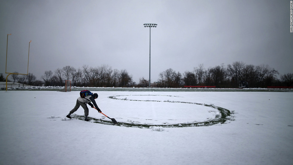 Hunter Gallagher uses a shovel to write a letter in his girlfriend's name in the snow on the football field at Catholic University on March 6 in Washington.