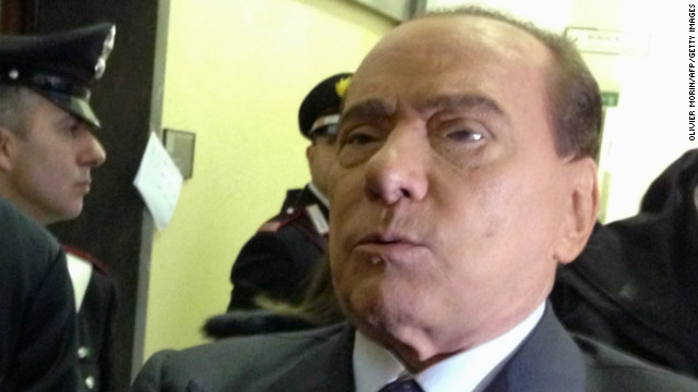 Former Italian Prime Minister Silvio Berlusconi reacts in a corridor of Milan's tribunal during a hearing of the Mediaset trial on March 1, 2013.