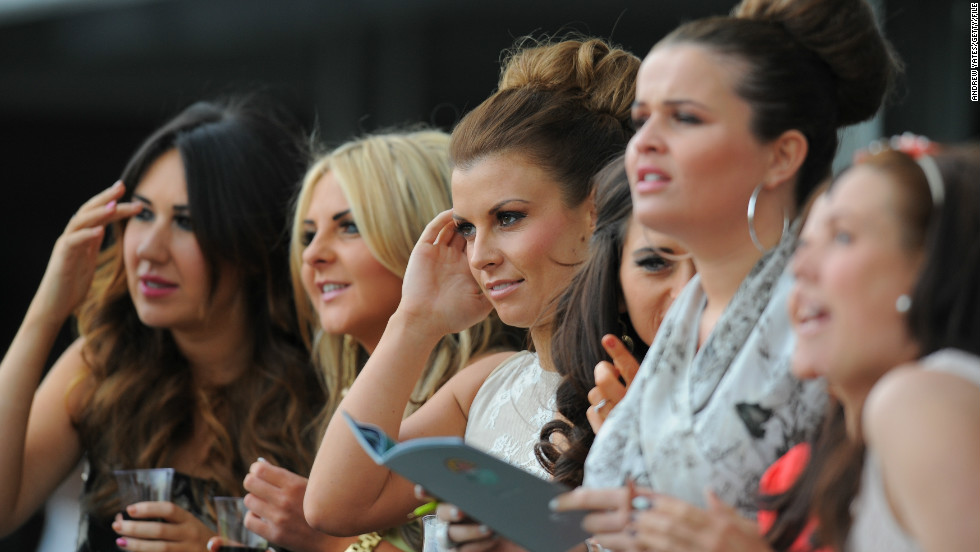 English Premier League football star Wayne Rooney's wife Coleen (center) watches the action from the race track. The couple own three race horses, including one called Switcharooney.