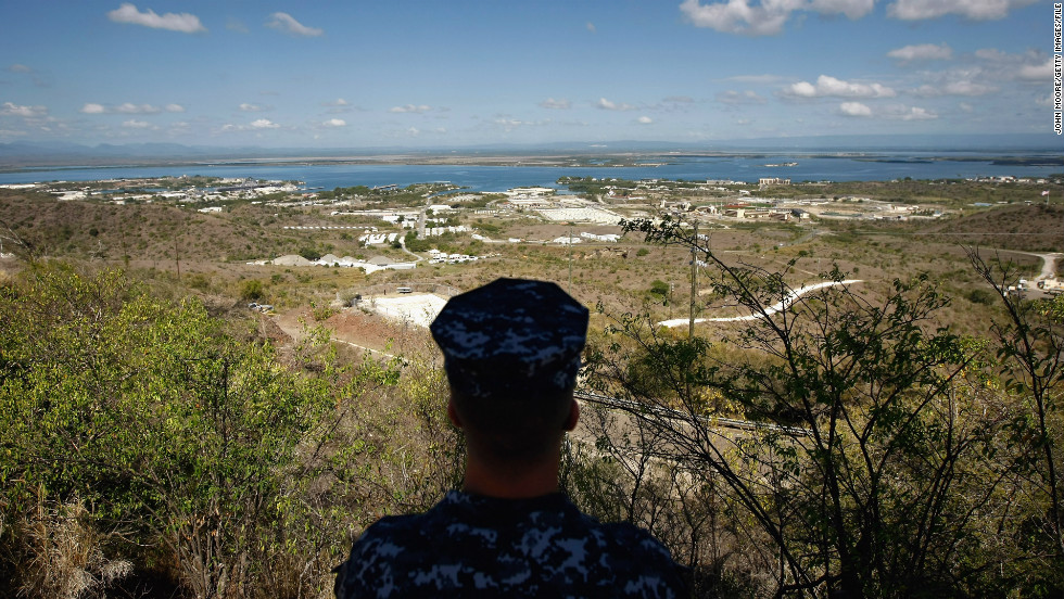 "A Navy sailor surveys the U.S. naval base at Guantanamo Bay in October 2009. In December 2013, Congress <a href=""http://politicalticker.blogs.cnn.com/2013/12/26/obama-signs-budget-defense-bills-in-hawaii/"" target=""_blank"">passed a defense spending bill</a> that makes it easier to transfer detainees out of the facility."