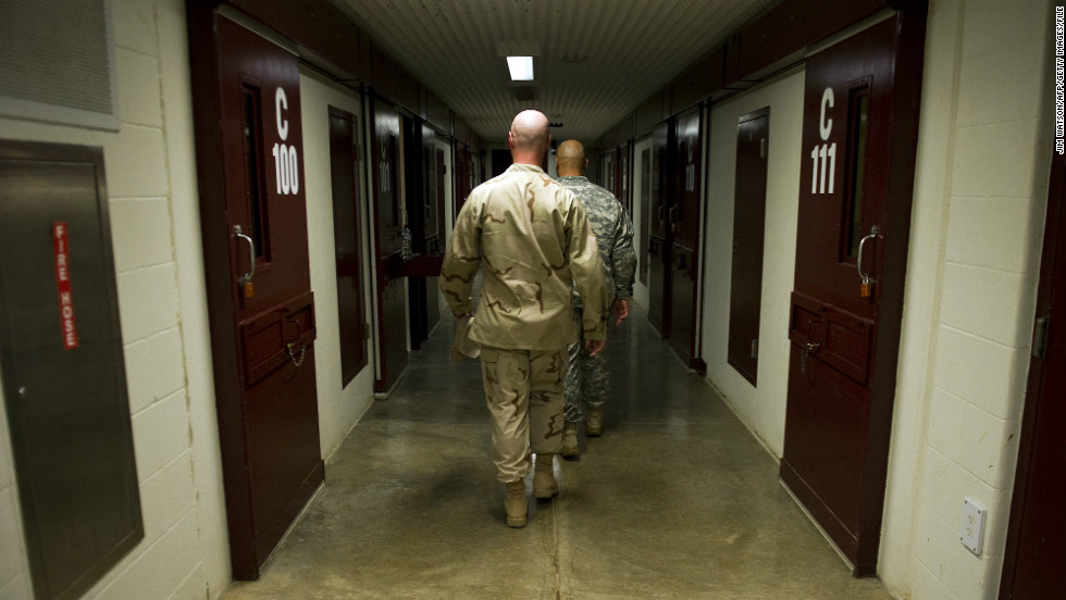 Members of the military walk the hallway of Cell Block C in the Camp 5 detention facility in January 2012.