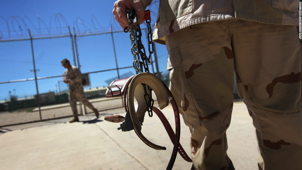 A U.S. military guard holds shackles before preparing to move a detainee in September 2010.