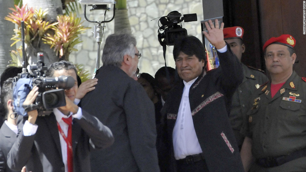 Bolivian President Evo Morales, center, waves next to former Paraguayan President Fernando Lugo outside of the funeral on March 8.