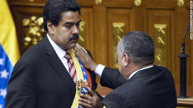 Diosdado Cabello (right) puts the presidential sash on Venezuelan Vice President Nicolas Maduro after he was sworn in as President in Charge, in Caracas.