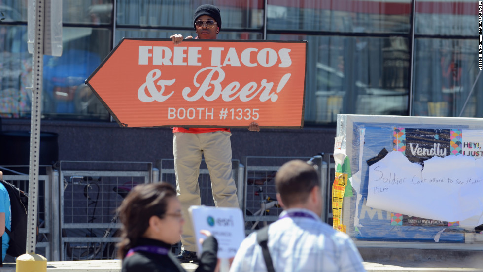 A man advertises free tacos and beer during SXSW on March 10.