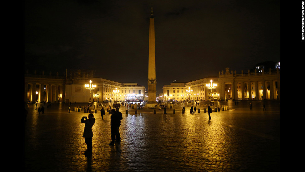 A few pilgrims are present in St. Peter's Square as night falls on Monday, March 11.