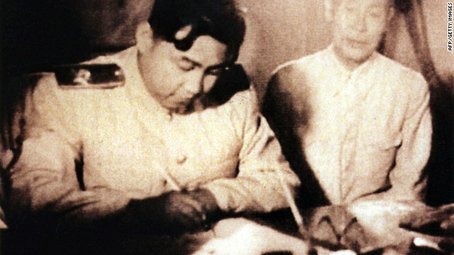This undated photo shows North Korean leader Kim Il Sung (L) as he signs a document in Seoul, Korea.