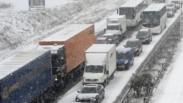Cars drive in the morning traffic on the N118 road around Paris, on March 12, 2013, during a heavy snow storm on France.