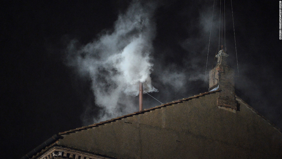 White smoke rises from the chimney on the roof of the Sistine Chapel.