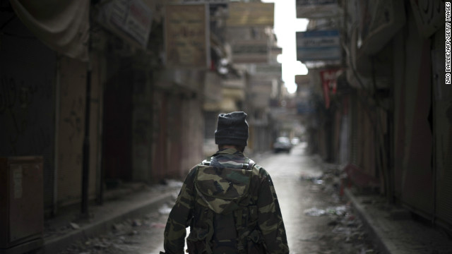 Rebel fighter walks through the ravaged Sit al-Ruba shopping street in the city of Deir Ezzor, Syria, on February 16, 2013.