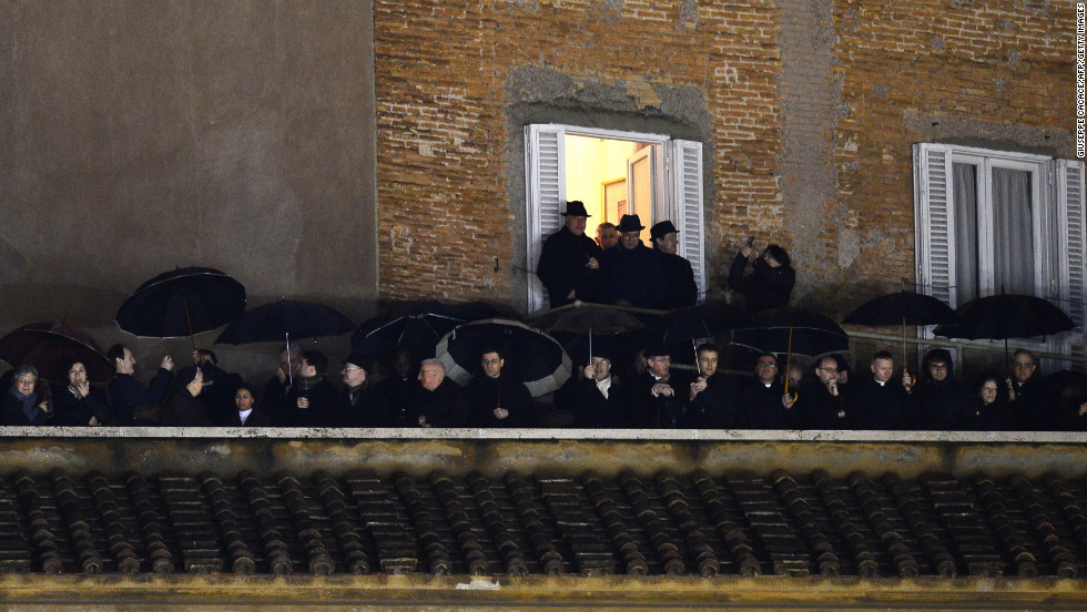 People stand on a balcony at St. Peter's Square as they wait for the identity of the new pope to be revealed.