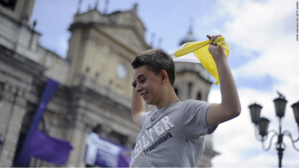 A young man waves a flag of the Vatican after the announcement of the election of Argentina's cardinal Jorge Bergoglio, as Pope Francis in Guatemala City.