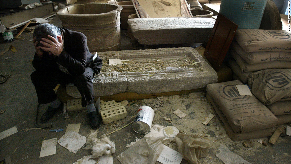 Iraqi National Museum Deputy Director Mushin Hasan sits among destroyed artifacts on April 13, 2003, in Bagdhad. The museum was severely looted.