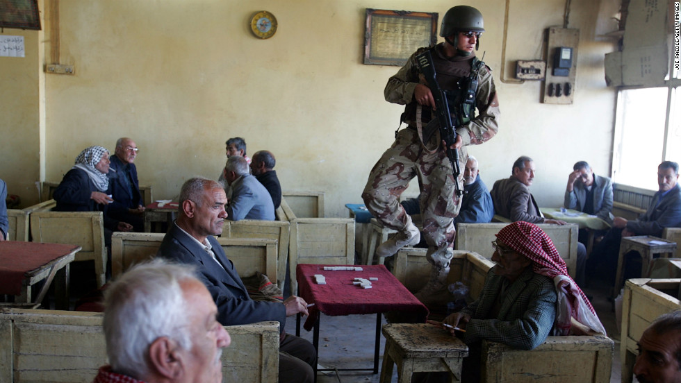An Iraqi soldier stands watch at a teahouse while on patrol with U.S. soldiers in Baghdad on February 23, 2005.