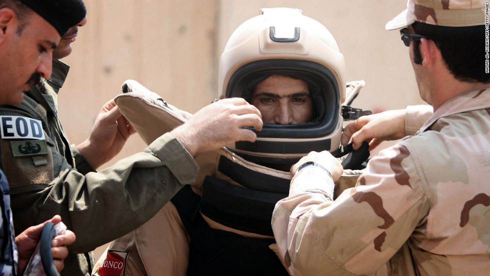 An Iraqi explosives expert gets into a special suit for bomb disposal during a training session organized by his U.S. counterparts at the Warhorse military base near the restive city of Baquba on August 17, 2010.