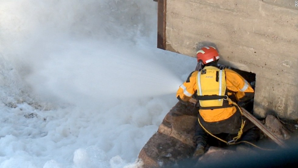 A searcher uses a hose to try to calm the foam caused by the rushing water in hopes it will increase visibility for the search.