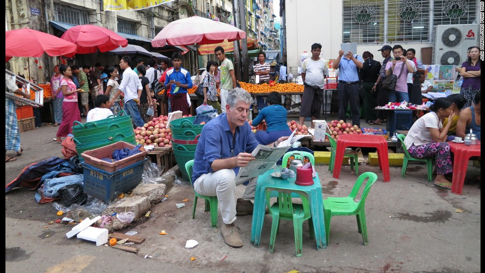 Bourdain reads a newspaper next to the local market in Yangon.