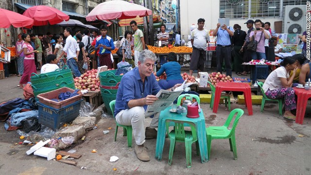 Anthony Bourdain reads the paper next to a local market in Yangon, Myanmar.