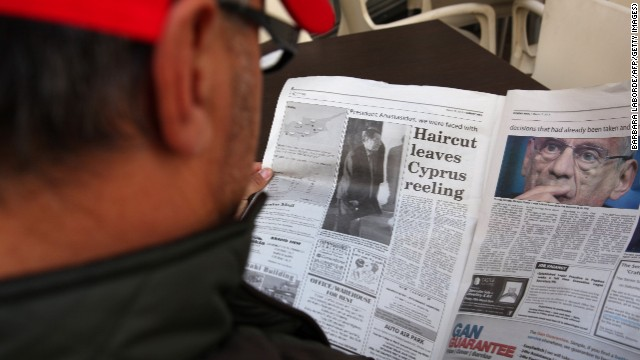 A man reads a newspaper at a cafe in the Cypriot capital Nicosia on March 17, 2013.