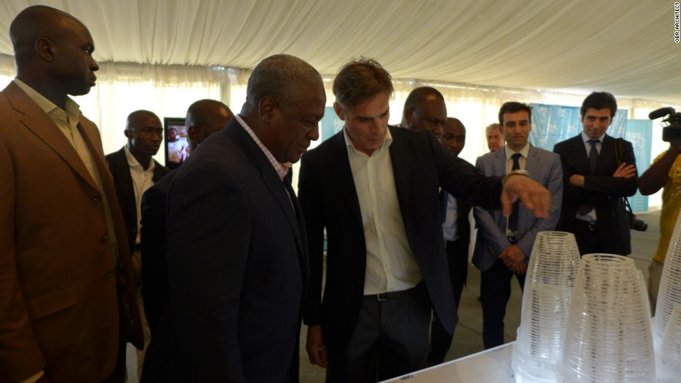 Italian architect Paolo Brescia (center) showcases the Hope City design to Ghanaian president John Mahama, standing next to him.