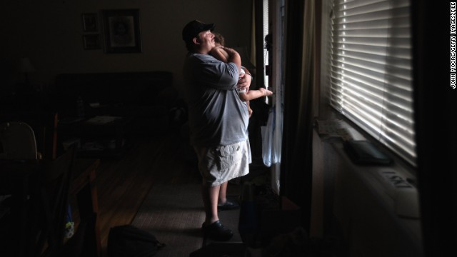 LAKEWOOD, CO - SEPTEMBER 24: Iraq War veteran Brad Hammond holds his son Cooper, 18-months, while looking from the front door of his house on September 24, 2011 in Lakewood, Colorado. Seven years after returning home from a year-long deployment in Tal Afar, Iraq, Hammond continues to experience severe post traumatic stress disorder (PTSD), and the effects of traumatic brain injuries he sustained in combat. He suffers from chronic anxiety, headaches, night terrors, hallucinations and frequent bouts of aggression and cannot hold down a full time job. He helps his wife Dani care for their three children, while also taking a private mentoring classes to help improve his attention and cognitive skills. Hammond was on a team of U.S. soldiers who opened fire on a carload of Iraqi civilians on January 18, 2005 in Tal Afar, Iraq, killing two, when they did not stop at a checkpoint. (Photo by John Moore/Getty Images)