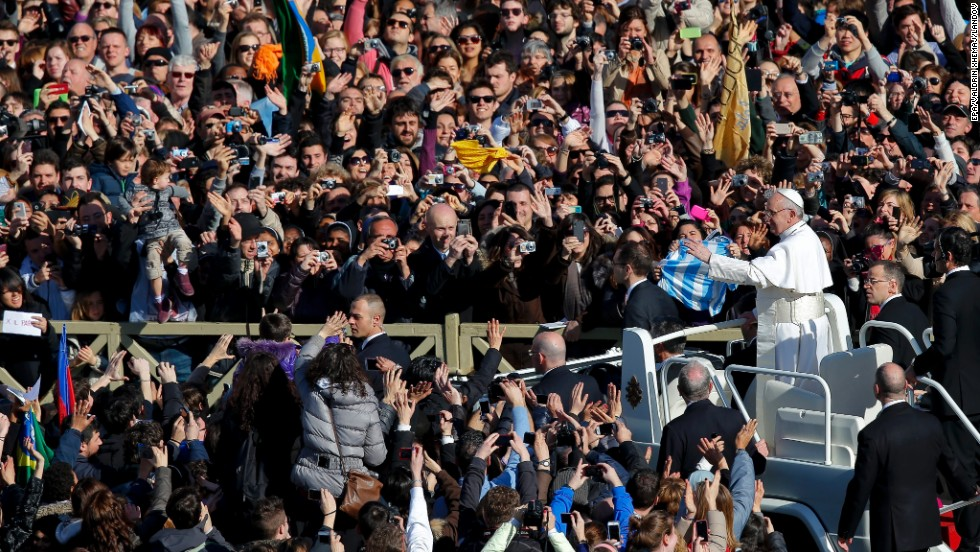 Pope Francis greets crowds as he arrives at St. Peter's Square.