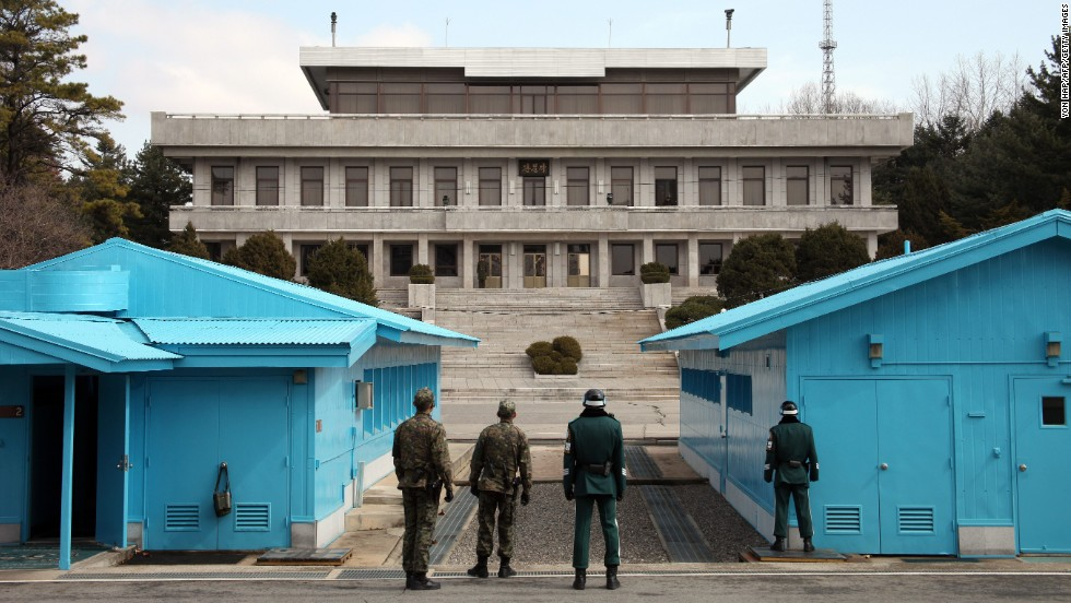 South Korean soldiers stand guard as a North Korean soldier, far center, looks on at the truce village of Panmunjom in the demilitarized zone dividing the two Koreas on March 13.