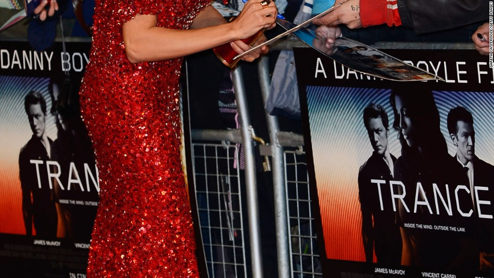"Rosario Dawson signs autographs for fans at the premiere of ""Trance"" in London."