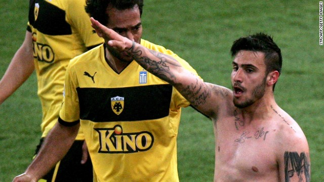 AEK Athens midfielder Giorgos Katidis, 20, issues the goal celebration that has placed his footballing career in jeopardy.