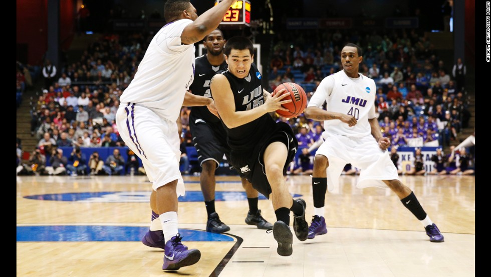 Jason Brickman of the LIU Brooklyn Blackbirds drives against Rayshawn Goins of the James Madison Dukes during the First Four round of the NCAA tournament on March 20, in Dayton. James Madison defeated LIU Brooklyn 68-55.