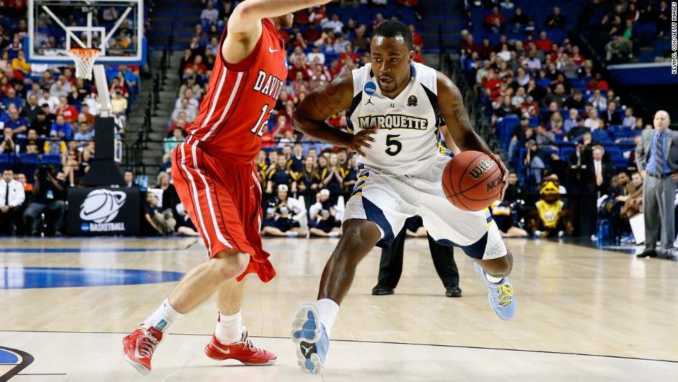 Junior Cadougan of the Marquette Golden Eagles drives against Nik Cochran of the Davidson Wildcats on March 21 in Lexington, Kentucky.