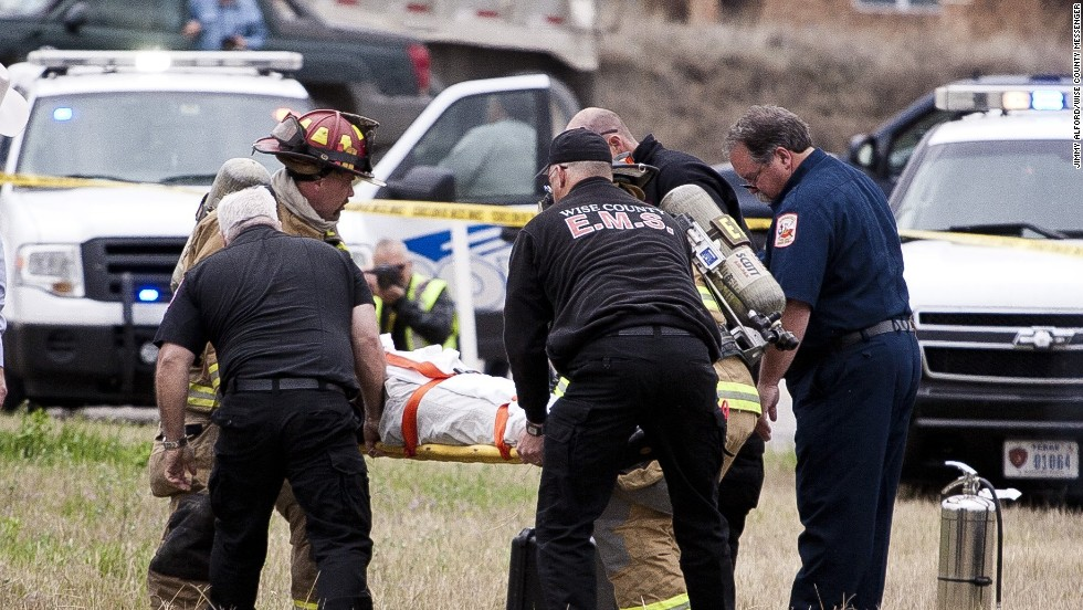 Firefighters and emergency workers carry Ebel to a waiting ambulance. He later died.