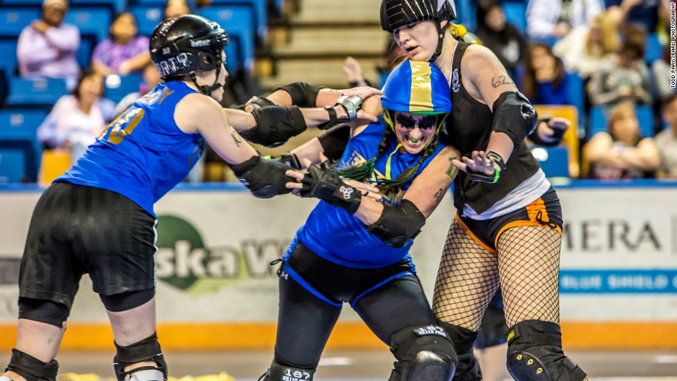 """Frazer, center, has since lost 100 pounds and upped her blocking skills. """"This is one of the reasons why I love playing the game!"""" she wrote in an e-mail."""
