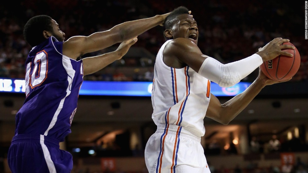 Will Yeguete of the Florida Gators, right, controls the ball against Marvin Frazier of the Northwestern State Demons on March 22.