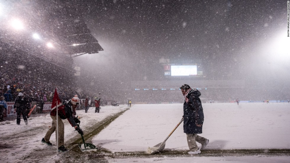A staffers shovel snow near the corner of the field as play continues in the inclement weather on March 22.