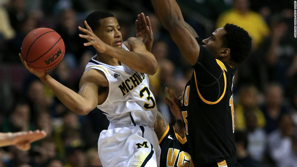 Trey Burke of the Michigan Wolverines, left, looks to pass against Juvonte Reddic of the Virginia Commonwealth Rams on March 23 in Auburn Hills, Michigan. The Wolverines won 78-53.