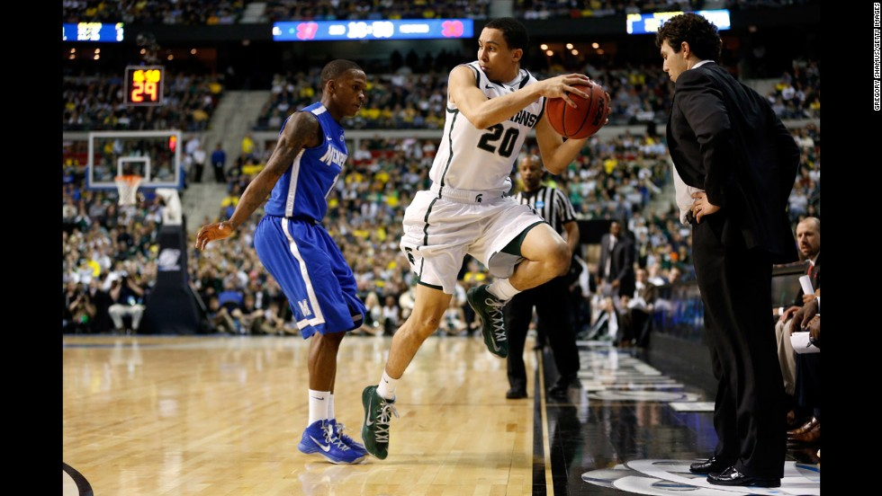 Travis Trice of Michigan State attempts to save the ball from going out of bounds while Joe Jackson of Memphis gives pursuit on March 23. Memphis coach Josh Pastner watches.