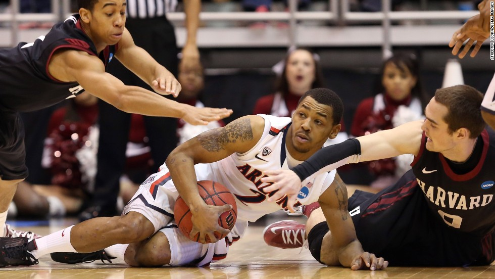 Arizona's Mark Lyons goes after a loose ball against Siyani Chambers, left, and Laurent Rivard, right, of Harvard on March 23.