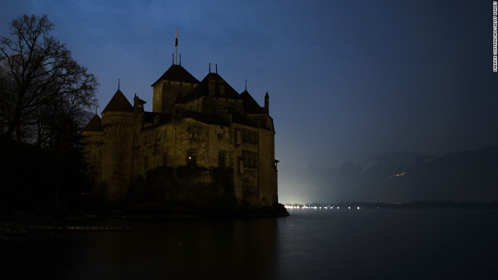 The silhouette of the Chillon Castle is seen with lights off on the edge of Lake Geneva near Montreux during Earth Hour.