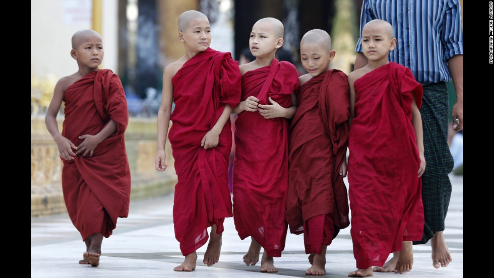 Young Buddhist monks walk on their daily alms collection at the sacred golden Shwedagon Pagoda in Yangon.