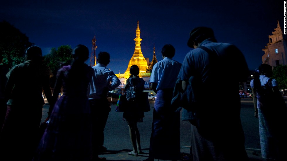 The Sule Pagoda lights up the night sky as people wait for the bus in Yangon. Pagodas serve as shrines for Theravada Buddhists, the majority religion in the country.
