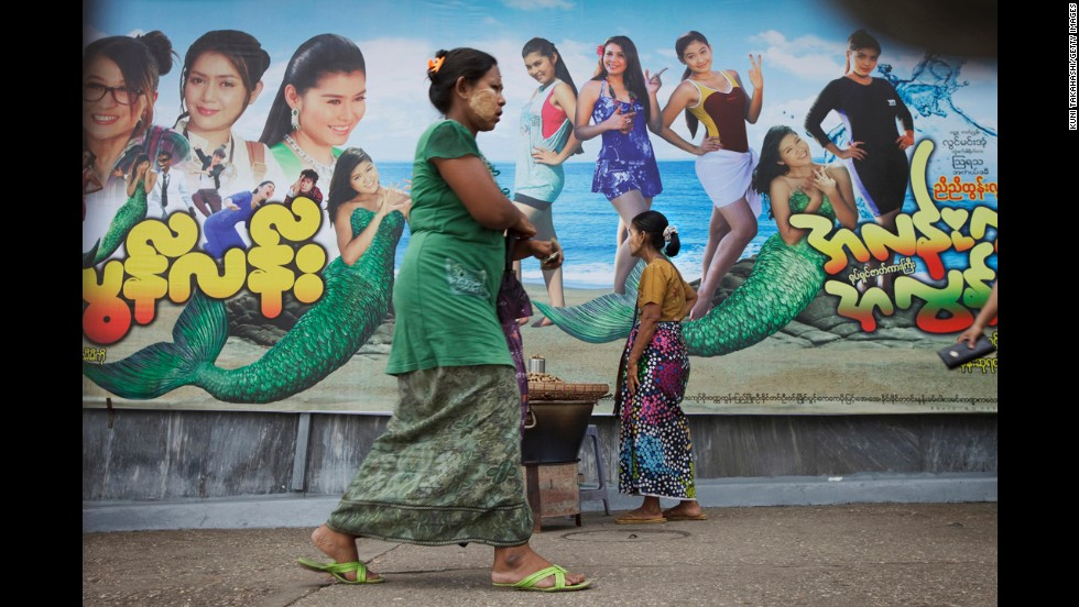 Women wear traditional longyi around their waists in front of a modern movie billboard in Yangon.
