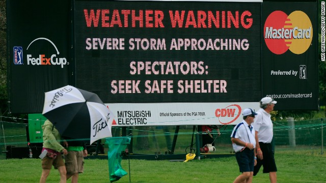 Fans seek shelter during the final round of the Arnold Palmer Invitational at the Bay Hill Club and Lodge in Orlando, Florida.