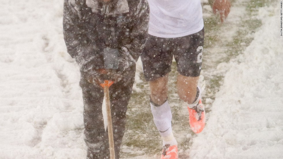 U.S. midfielder Geoff Cameron lends a hand as an official attempts to clear snow off the pitch markings.
