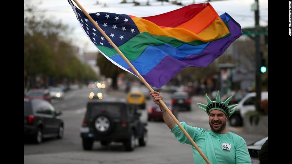 Nikolas Lemos waves a rainbow flag during the March 25 rally in San Francisco.