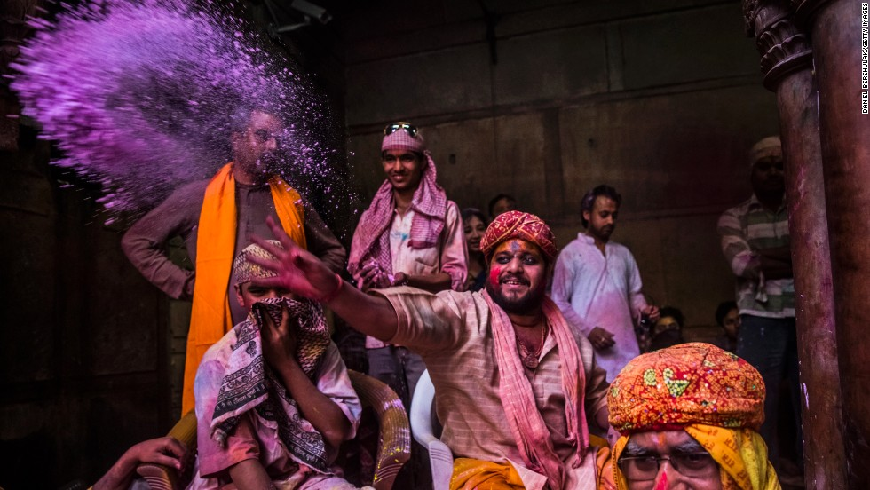 A Hindu priest throws colored powder at devotees on March 26 in Vrindavan.