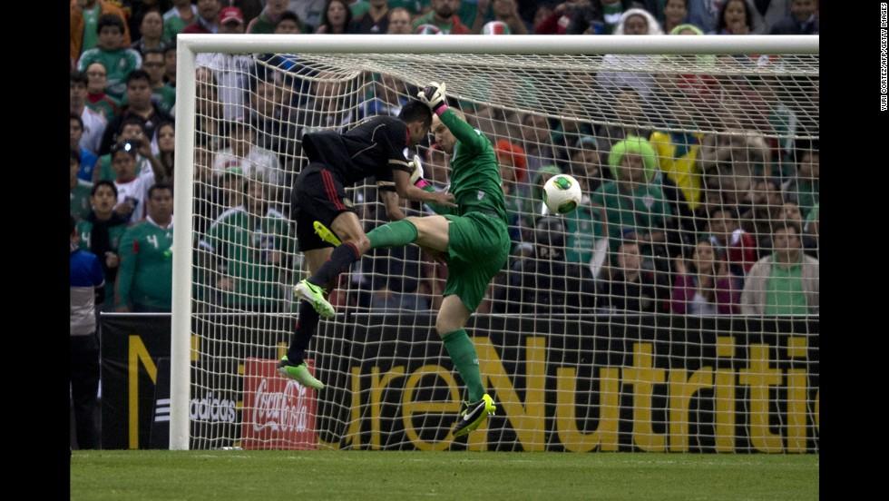 Mexico's Jesús Zavala and U.S. goalkeeper Brad Guzan fight for the ball.