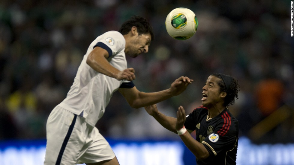 The U.S.'s Omar Gonzalez tries to head the ball as Mexico's forward Giovani dos Santos challenges.